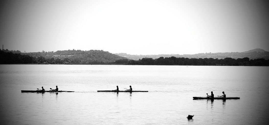 People sculling in lake against sky