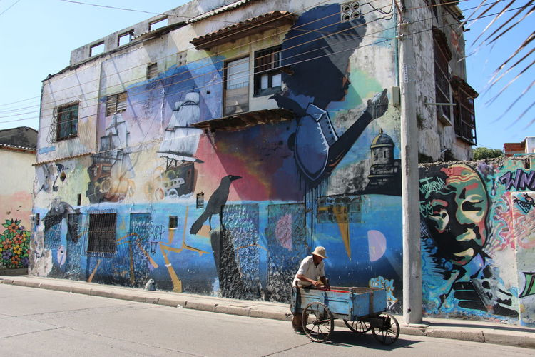 Street Art - one man with wagon Adult Architecture Art Black Girl Building Exterior Built Structure Carriage Culture Damaged Day Man One Person Outdoors Painting Person Ship Sky Spray Paint Trolly Wagon