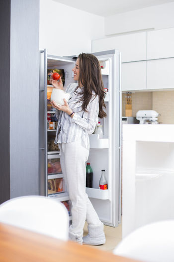 Smiling young woman taking food from refrigerator