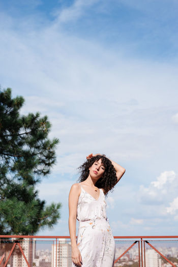 Woman with curly hair standing against sky