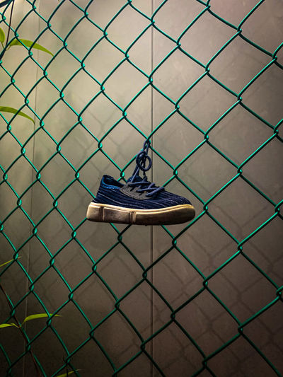 High angle view of shoes hanging on chainlink fence