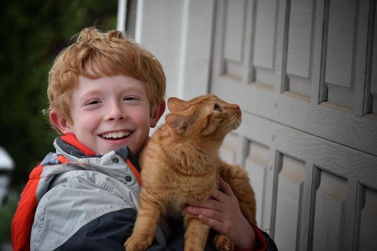 Portrait Of Happy Boy With Cat Standing By Door