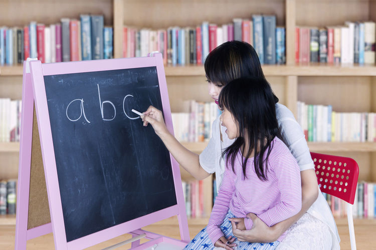 Smiling Young Woman Teaching Daughter Alphabets On Blackboard At Home