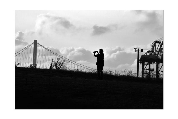 Silhouette man photographing bridge against sky