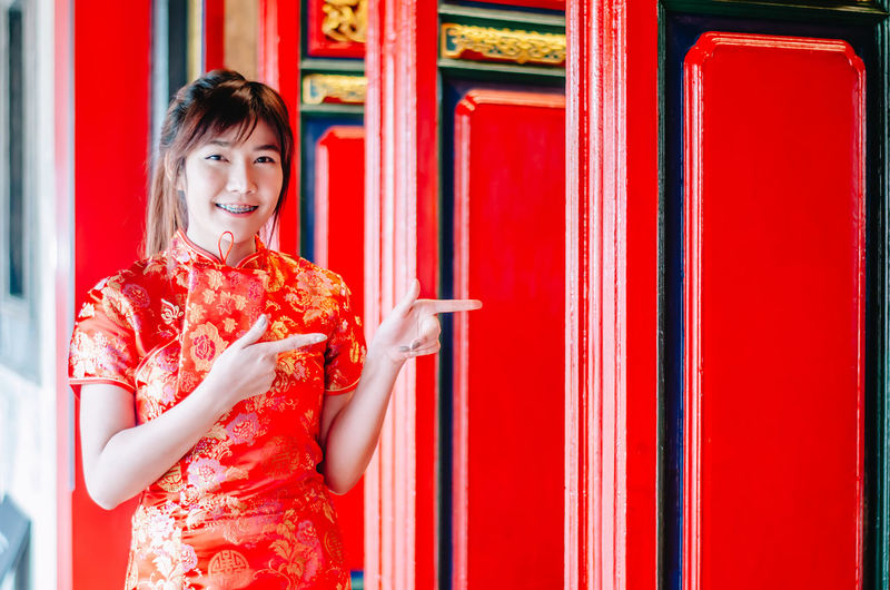 Chinese girl in traditional Chinese cheongsam pointing at china temple and introduce something to you in chinese new year ASIA Asian  Attractive Background Beautiful Beauty Cheerful Cheongsam China Chinese Clothing Copy Culture Door Dress Elégance Empty Female Finger Gesture Girl Hand Happy Human Introduce Lady Mandarin Model New Oriental People person Pointing Pose Pretty Qipao Red Show Sign Smile Space Temple Traditional View Wear White Woman Women Year Young
