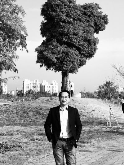 Portrait of mature man standing against tree and sky