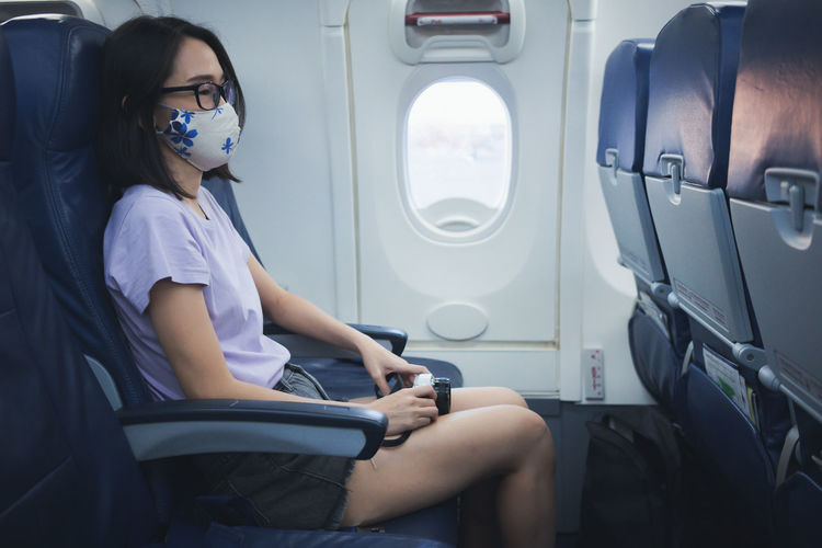 Rear view of woman sitting in airplane