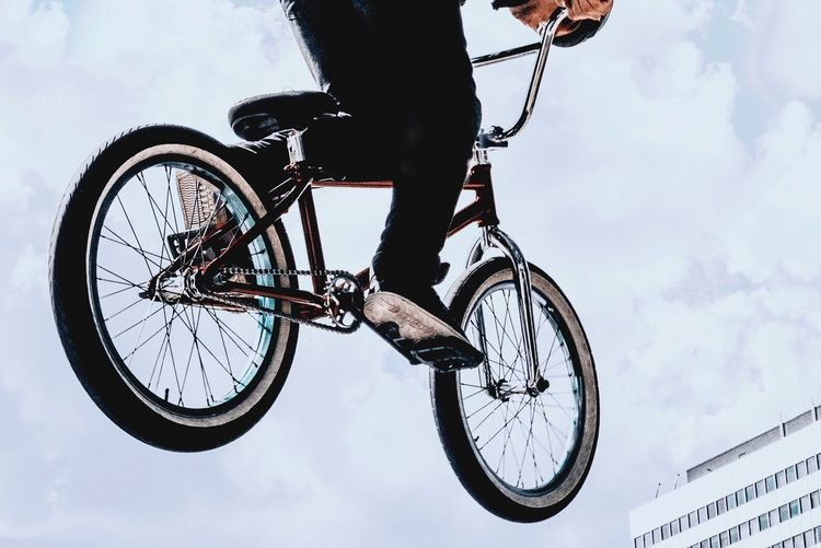 Low Section Of Man Riding Bicycle Against Sky