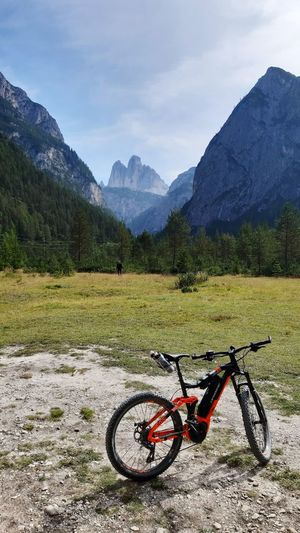 Bicycle on field by mountains against sky