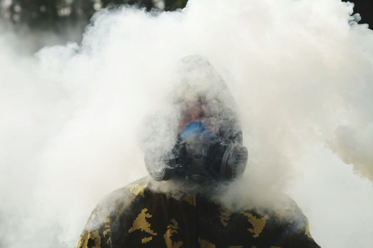 Portrait of young man in gas mask standing amidst smoke