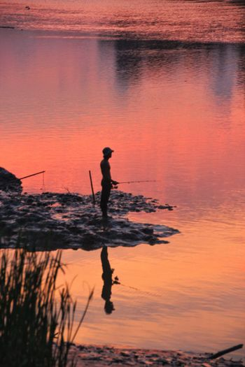 Silhouette man fishing while standing in lake against orange sky