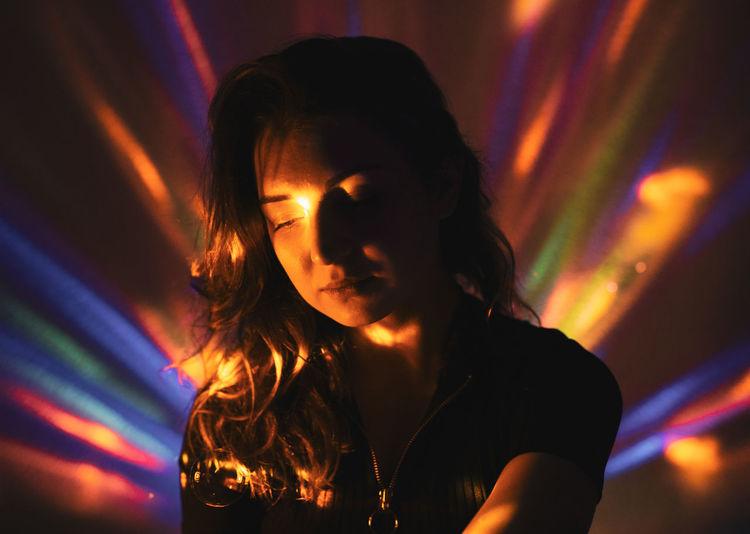 Thoughtful woman in illuminated nightclub