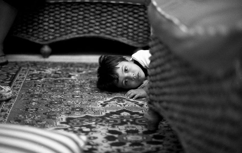 Portrait of cute boy lying on carpet at home