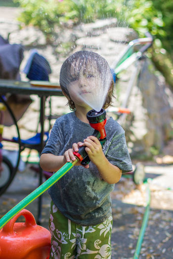 Boys Casual Clothing Child Childhood Close-up Cute Day Focus On Foreground Full Length Holding Hose Leisure Activity Lifestyles One Boy Only One Person Outdoors People Playing Playing With Water Real People Standing Summer Wet