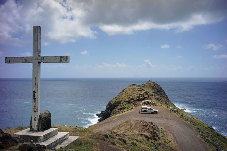 Cross and cliff by sea against cloudy sky