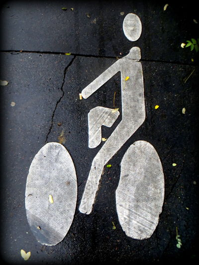 OO - Bike Rider very Laid Back Asphalt Bicycle Bicycle Road Bicycles Bicycling Close-up Day Directional Sign Geometric Shape Guidance Information Sign No People OO Mission Outdoors Road Road Marking Road Sign Street The OO Mission