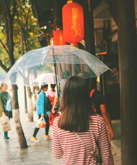 Rear View Of Woman Walking With Umbrella On Sidewalk During Monsoon