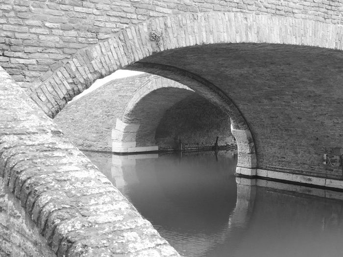 Arch Arch Bridge Architectural Feature Architecture Archway Blackandwhite Bridge Bridge - Man Made Structure Built Structure Canal Comacchio Comacchiocity Comacchiopiccolavenezia Connection Curve Day Engineering Flowing No People River Stone Material The Way Forward Tunnel Water Waterfront