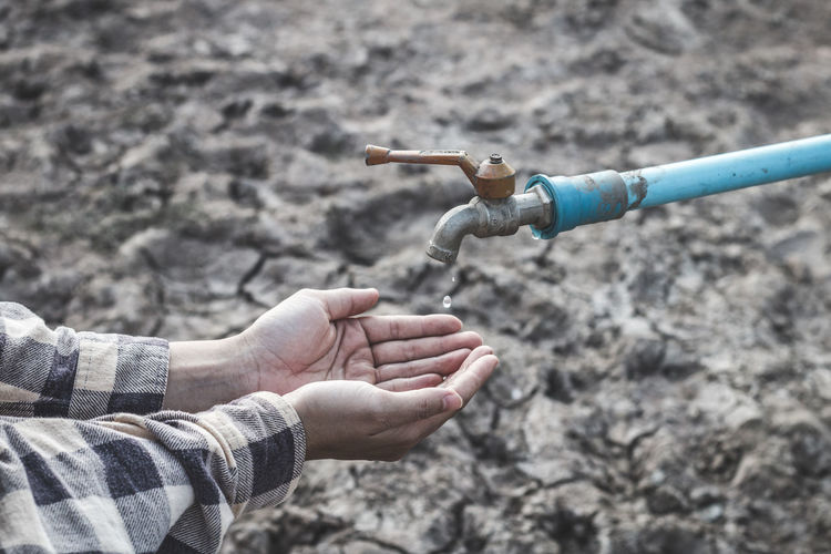 Cropped image of hands catching water drop falling from faucet during drought
