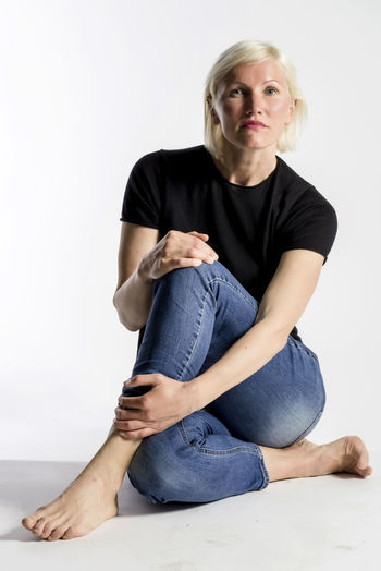 Portrait of attractive young blond woman sitting on floor and looking at camera isolated on white background One Person Front View Indoors  Studio Shot Portrait Casual Clothing Looking At Camera Sitting Women Adult White Background Blond Hair Full Length Young Adult Young Women Hair Lifestyles Females Hairstyle Jeans Beautiful Woman Females Modelling Model Blonde Girl Lady Looking At Camera Sitting Ground Flooring
