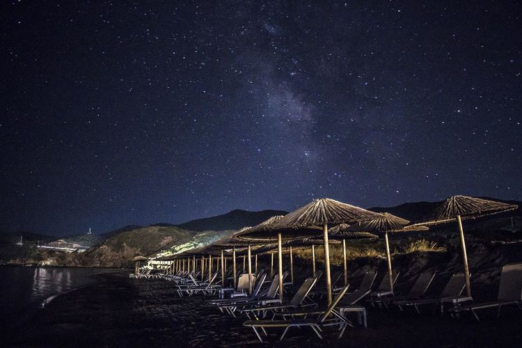 Thatched roofs and lounge chairs at beach at night