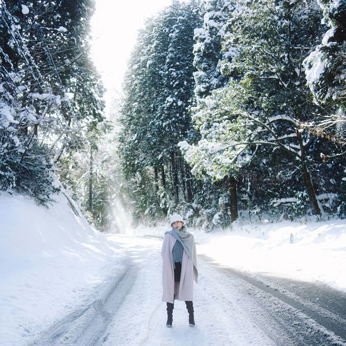 Woman standing on road amidst trees during winter