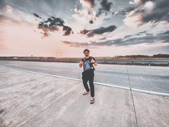 Full length of man standing on road against sky during sunset