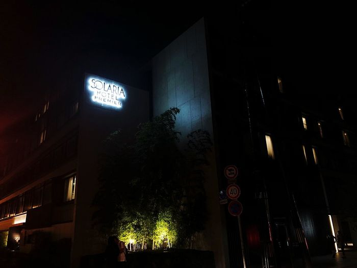 Low angle view of illuminated sign on building at night