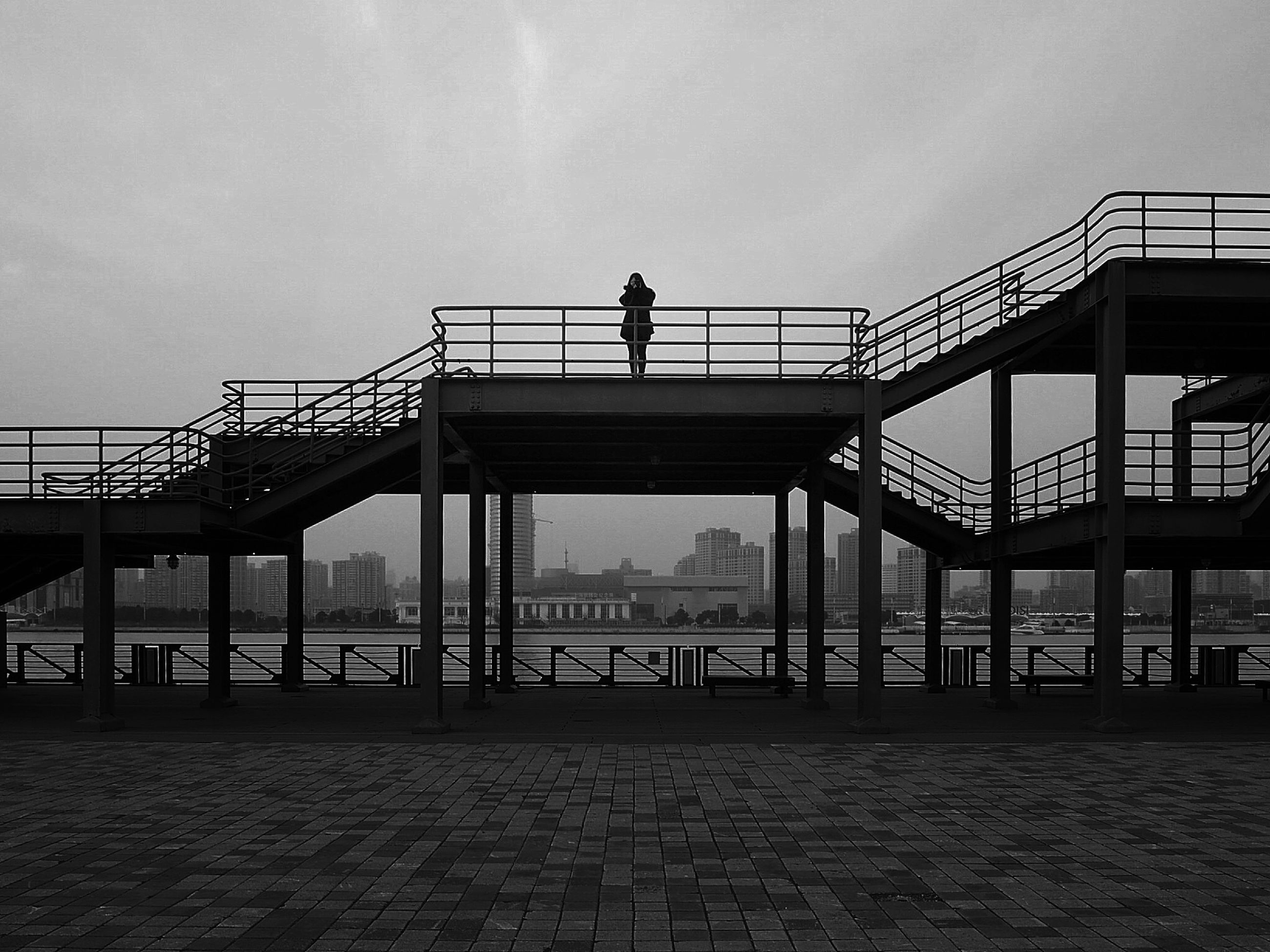 built structure, architecture, silhouette, men, sky, railing, standing, lifestyles, full length, walking, leisure activity, rear view, building exterior, sunset, person, bridge - man made structure, unrecognizable person, outdoors