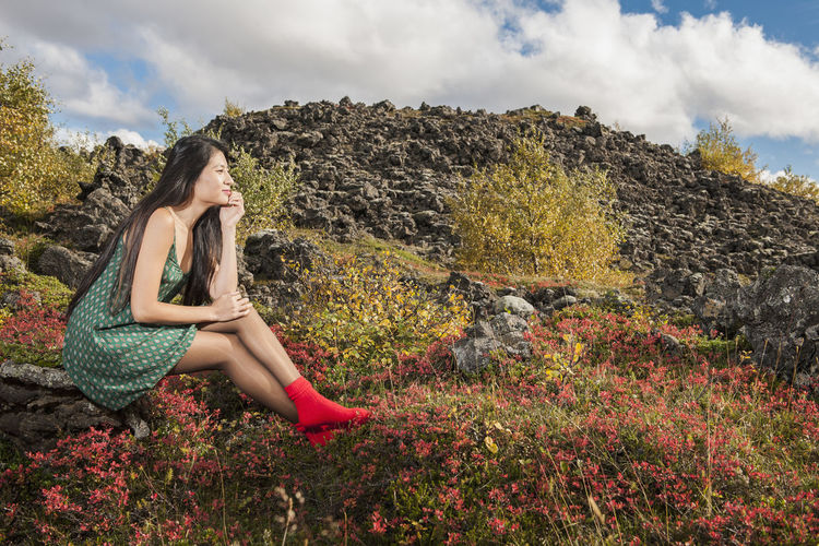 Side view of woman sitting on land against sky