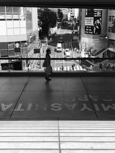 Rear view of woman walking on glass in city