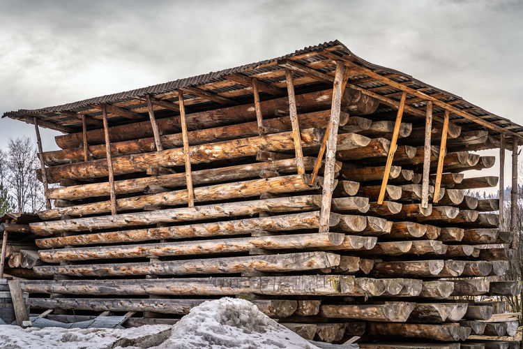 Stack of old wooden house against sky during winter