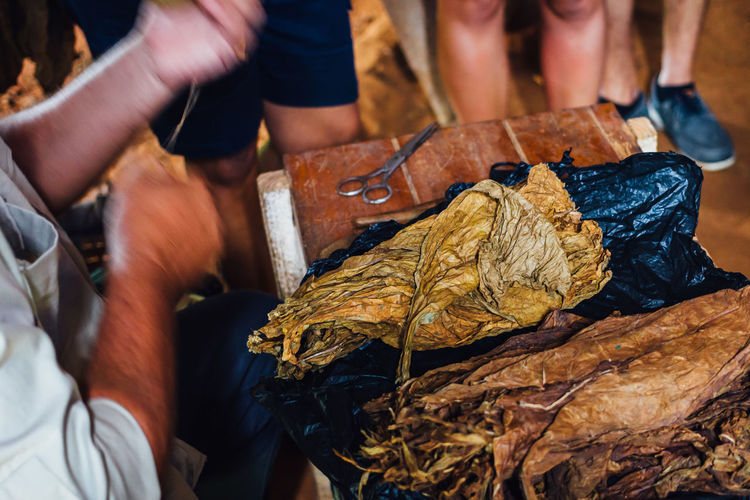 Cropped Image Of Vendor With Tobacco Leaf At Table