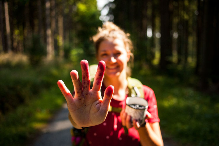 Portrait of woman showing stain on hand in forest