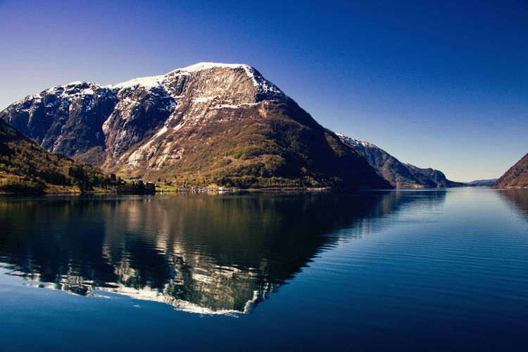Odda, Norway Mountain Scenics - Nature Tranquil Scene Sky Beauty In Nature Water Tranquility Reflection Blue Clear Sky Mountain Range Waterfront Nature Idyllic Day Non-urban Scene No People Copy Space Outdoors Snowcapped Mountain Formation Fjord Odda Norway Scandinavia Travel Destinations Travel Traveling Adventure Hiking