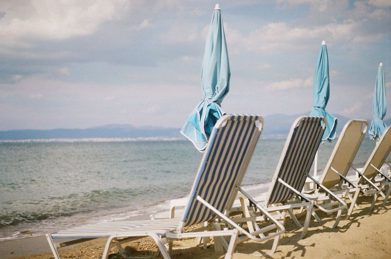 Deck chairs and closed parasols at beach against sky