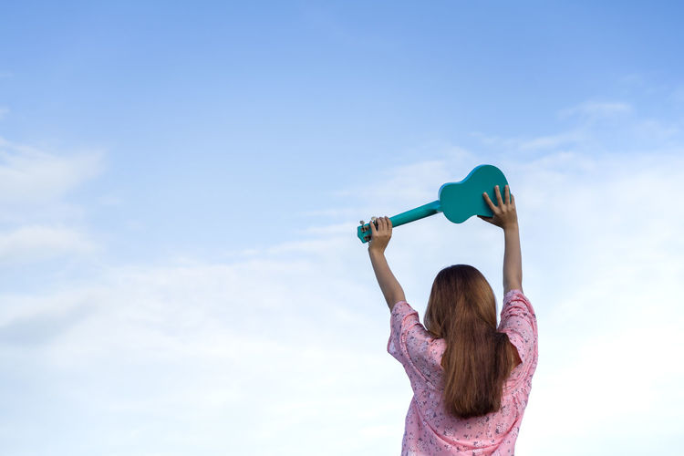 Rear view of woman holding ukulele against sky