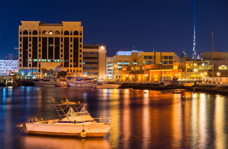 Boats moored at harbor by buildings in city at night