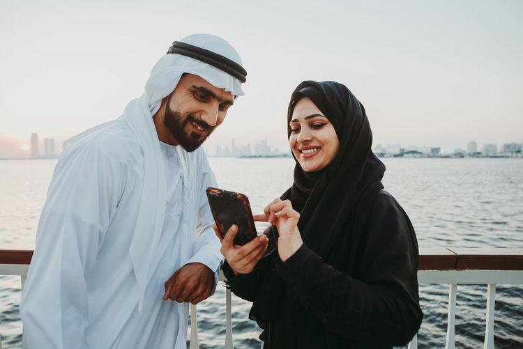Young man using phone while looking at camera