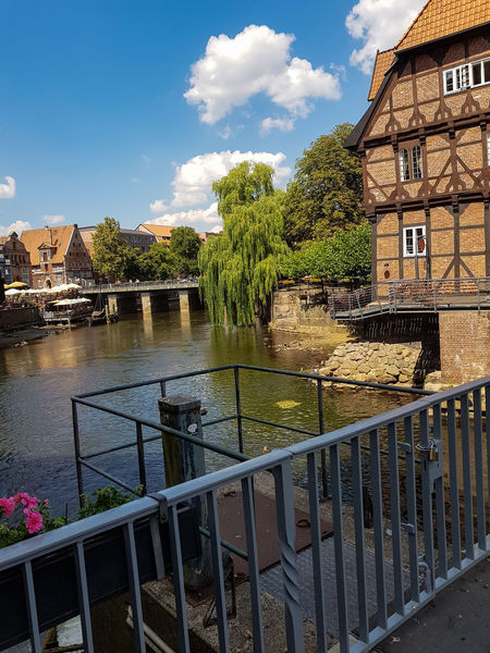 Half-timbered red brick houses near the river on the old harbor Lueneburg, Germany Built Structure Architecture Building Exterior Water Sky Cloud - Sky Railing Plant Nature Building River Tree No People Day Connection Travel Destinations City Bridge Outdoors