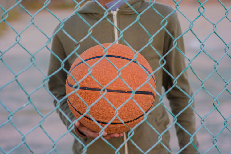 Defense Ball Barrier Basketball - Ball Basketball - Sport Boundary Chainlink Fence Close-up Day Fence Focus On Foreground Net - Sports Equipment No People Orange Color Outdoors Pattern Protection Safety Security Selective Focus Sport Sports Equipment