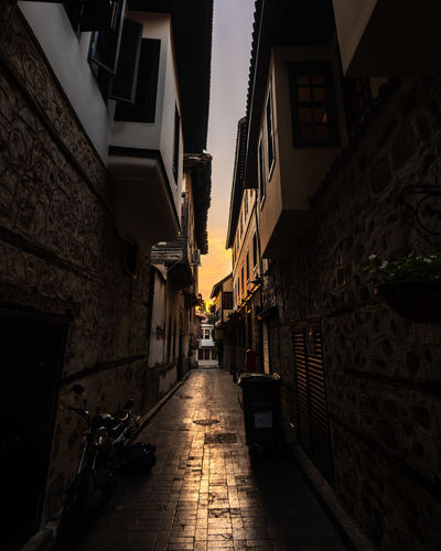 Empty Alley Amidst Buildings In City At Sunset