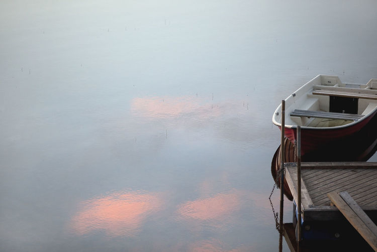 Rowboat moored at calm lake during sunset