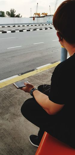 Bus stop Bus Stop Sitting Technology Wireless Technology Sea Men Shadow Sky Text Messaging Mobile Phone Smart Phone Using Phone