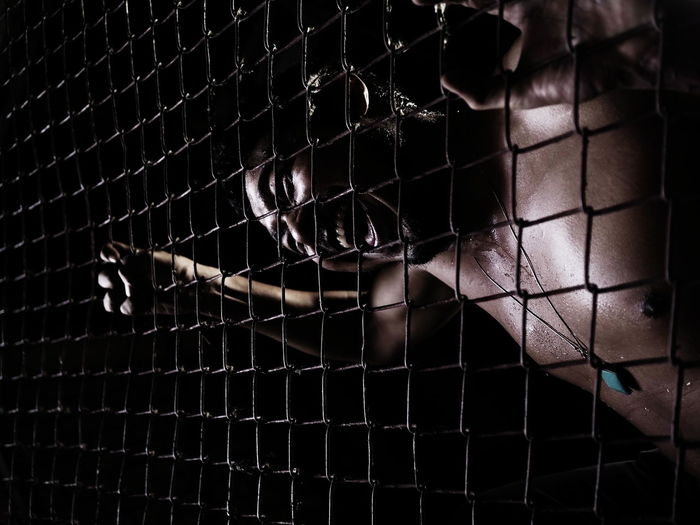 Angry shirtless man seen through chainlink fence