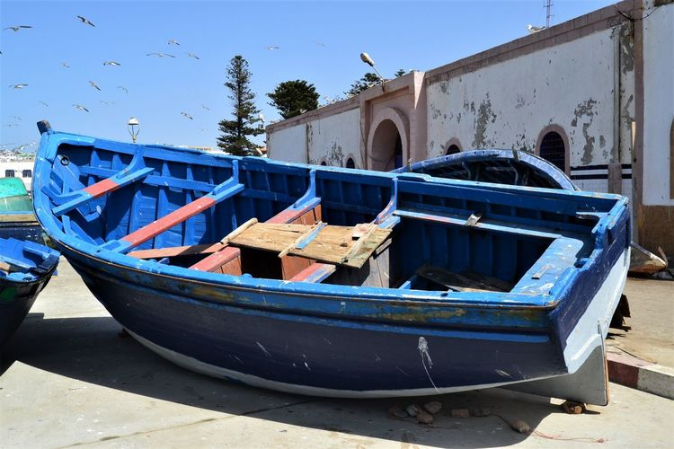 Wooden blue fishing boat tilted on its' side on dry land at Essaouira fishing port. Nautical Vessel Transportation Moored Mode Of Transportation Nature Day Water Blue Sky No People Architecture Outdoors Built Structure Clear Sky Beach Rowboat Old Land Building Exterior Fishing Boat Essaouira Boat Blue Boat Wooden Boat