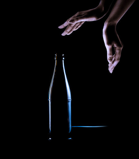 Close-up of hand holding glass bottle against black background