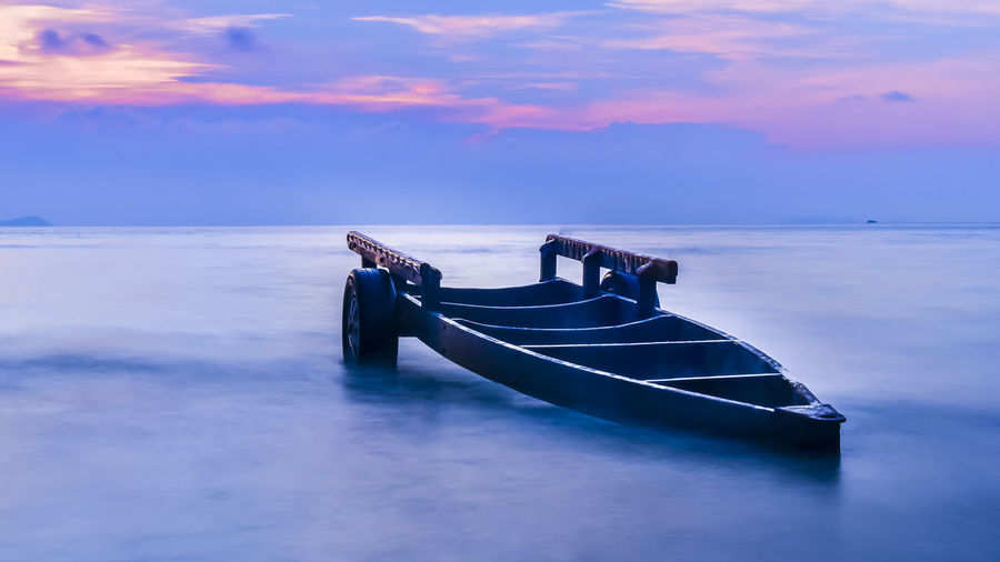 Old boat at sea shore against cloudy sky during sunset