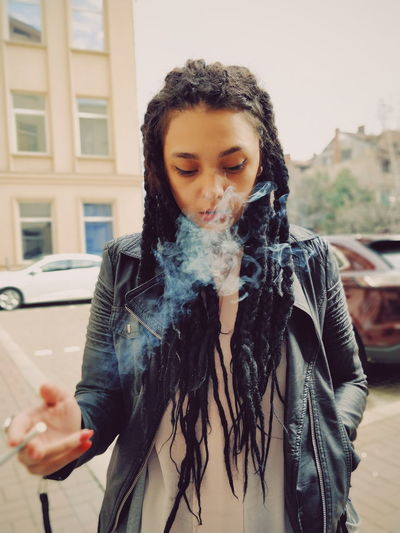 Young woman exhaling smoke while standing on street