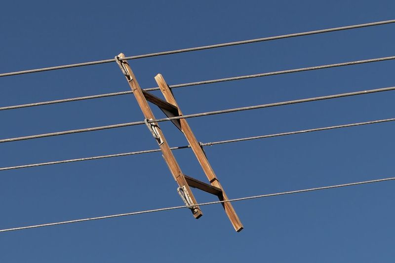 Low Angle View Of Wooden Frame On Pylon Lines Against Clear Sky